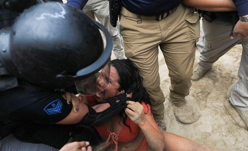 Momento cuando agentes de la Policía sacan a la fuerza a una manifestante.