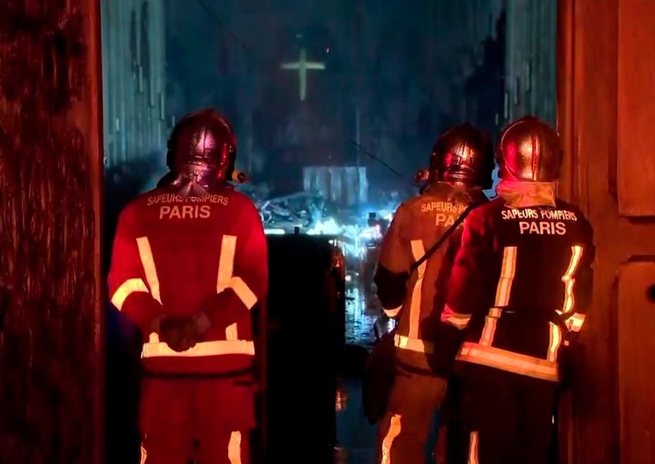 Los bomberos se asoman por la puerta de la catedral y al fondo se ve una cruz todavía de pie. (AP)