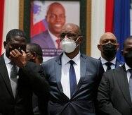 El primer ministro designado Ariel Henry, al centro, y el premier interino Claude Joseph, derecha, posan para una fotografía con otras autoridades frente a un retrato del presidente asesinado Jovenel Moïse en el Museo del Panteón Nacional, en Puerto Príncipe, Haití.