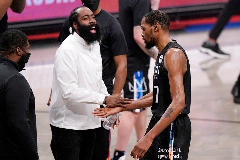 James Harden, en la foto felicitando a su compañero de los Nets Kevin Durant, se lesionó en el inicio del primer juego de la serie contra Milwaukee.