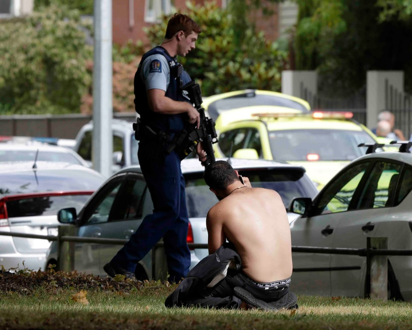 Un hombre descansa en el suelo mientras habla por su teléfono celular del otro lado de la calle de una mezquita en Christchurch, Nueva Zelanda. (AP)
