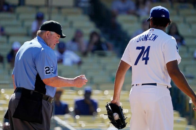 En esta foto del 13 de junio, el árbitro Joe West (izquierda) mira una pelota que el lanzador de los Dodgers de Los Ángeles Kenley Jansen había usado luego de darle una nueva durante el juego entre esa novena y los Rangers de Texas.