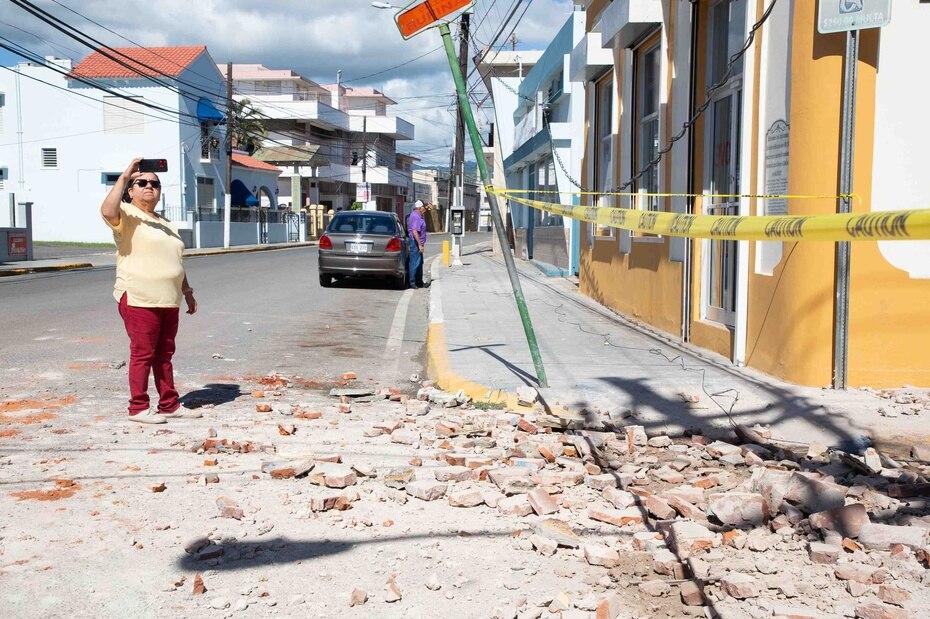 Una mujer captura una foto de los escombros que quedaron en la carretera al colapsar una estructura en Guayanilla.