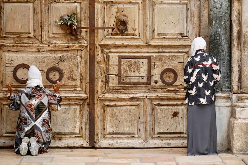 Unas mujeres rezan frente a una iglesia cerrada en Jerusalén, el domingo 5 de abril de 2020. (AP)