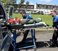 Los paramédicos Luis O. García  y Jonathan Pinto colocan una camilla en una ambulancia.