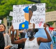 In this Saturday, June 13, 2020, photo, protesters demonstrate, in Salt Lake City. Protesters around the world and in Utah have rallied against police brutality and racism for more than two weeks after the death of George Floyd, a black man held in a neck hold by police in Minneapolis. (AP Photo/Rick Bowmer)