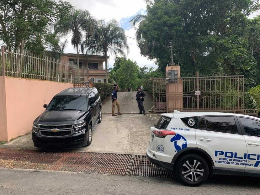 """Los agentes a las afueras de la casa del alcalde de Mayagüez, José """"Guillito"""" Rodríguez."""