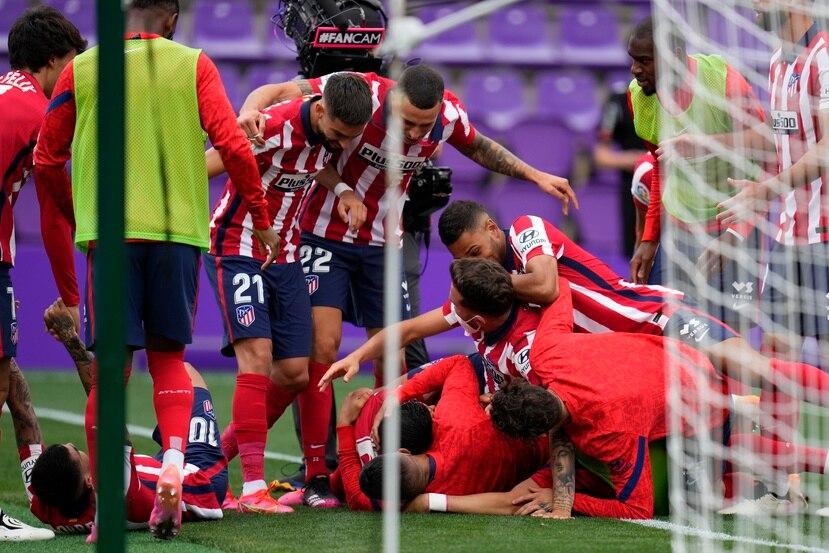 Los jugadores del Atlético de Madrid celebran con Luis Suárez luego que éste anotó el segundo gol del Atlético de Madrid en la victoria 2-1 contra Valladolid y que aseguró al equipo el campeonato del torneo nacional.