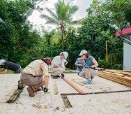 Voluntarios de SBP trabajan en el techo de una residencia.