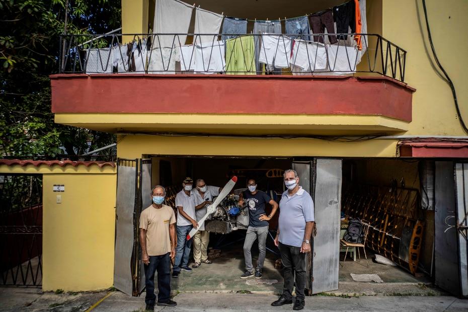 Adolfo Rivera, a la izquierda, junto a quienes lo ayudaron a construir una avioneta biplaza de madera, detrás, posan para una foto con el presidente del Club de Aviación de Cuba, René González, a la 0derecha, en el garaje de su edificio de departamentos en La Habana, el viernes 19 de febrero de 2021.