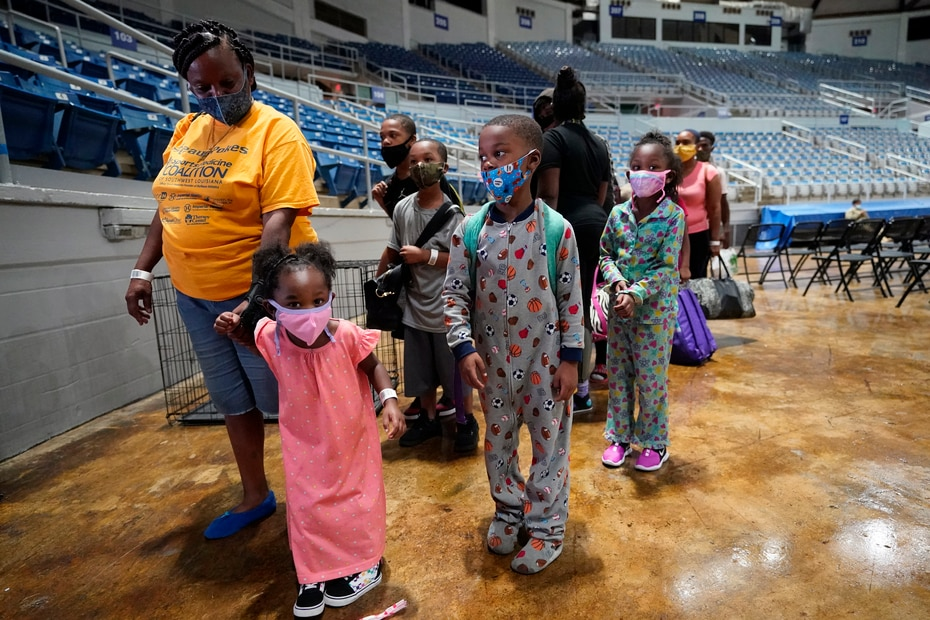 Victoria Nelson y sus hijos,  Autum Nelson, 2, Shawn Nelson, 7, y Asia Nelson, 6, aguardan para abordar un autobus en Louisiana.