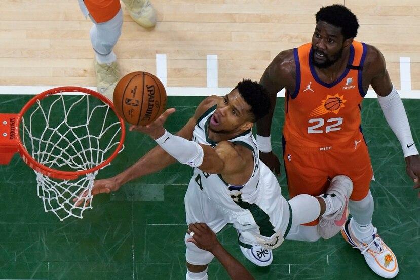Giannis Antetokounmpo (34) tira al canasto contra el centro Deandre Ayton (22) durante el cuarto juego de las Finales de la NBA.