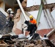 Rescatistas chilenos sostienen un perro especializado en rescates durante una búsqueda entre escombros en Beirut.