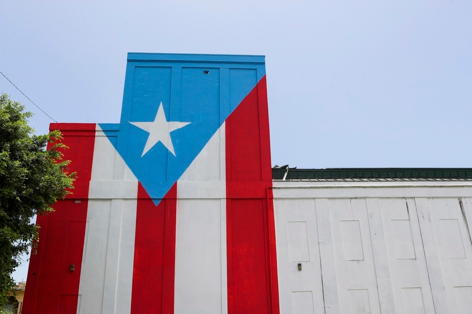 """La bandera #68 de la iniciativa """"78 pueblos, una bandera"""" está en una de las paredes del Teatro Municipal Ramón Rivero """"Diplo"""", que está ubicado frente a la plaza pública."""