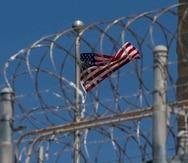 La foto de archivo del 17 de abril de 2019 revisada por oficiales militares estadounidenses muestra la bandera de Estados Unidos ondeando sobre la alambrada de púas del campo de detención VI en la base naval de Guantánamo, Cuba. (AP)