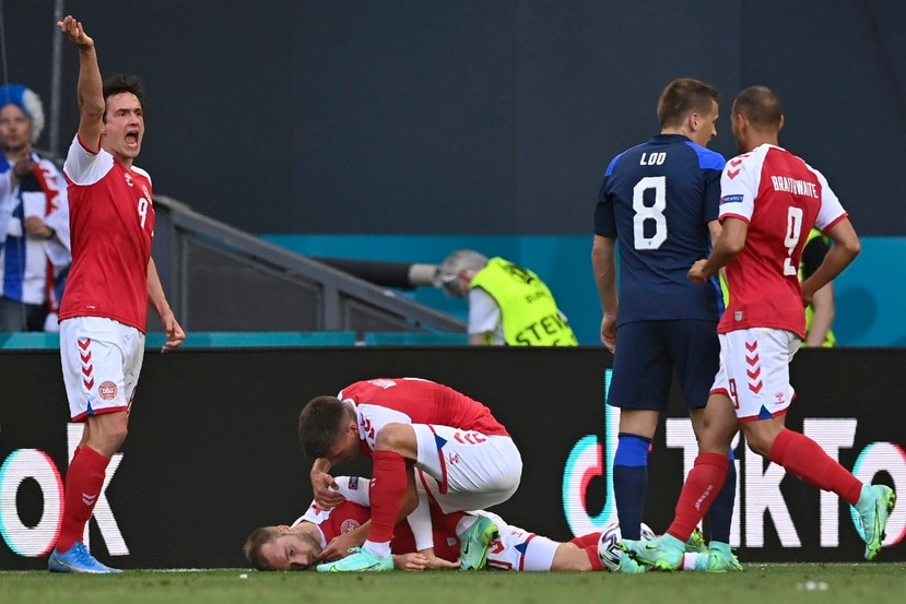 Jugadores de la selección de Dinamarca tratan de socorrer a su compañero Christian Eriksen, quien se desvaneció durante un partido de la Eurocopa ante Finlandia, el sábado 12 de junio en Copenhague.