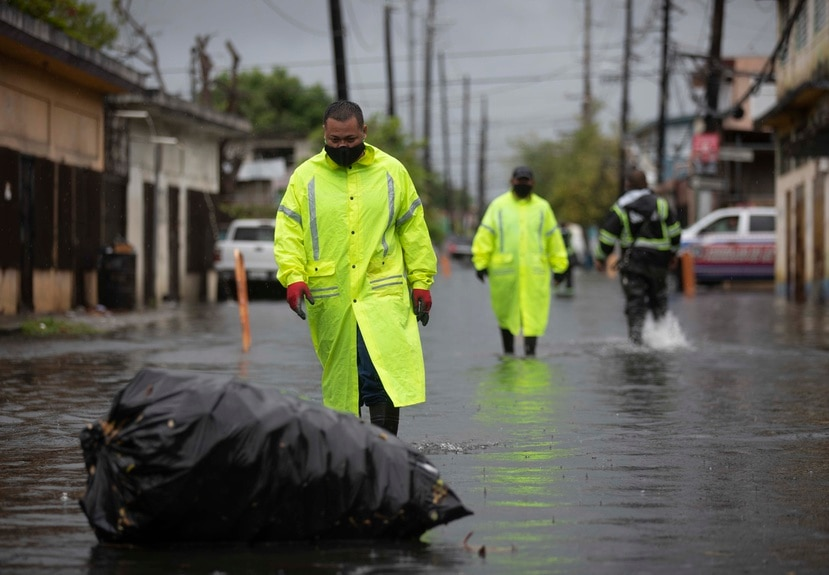 Empleados del Municipio de San Juan recorren las calles de Barrio Obrero para inspeccionar el área tras las inundaciones provocadas por el paso de la tormenta Isaías.