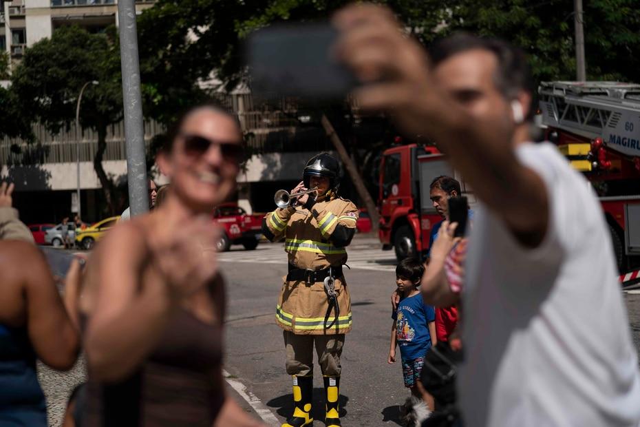 Residentes se toman un selfie mientras un bombero toca su trompeta,