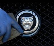 Un trabajador pule un logo de Jaguar en una concesionaria de la automotriz, en Londres.