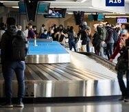 Viajeros esperan su equipaje en el aeropuerto Dallas/Fort Worth el 23 de diciembre del 2020.