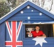 Novak Djokovic posa con el trofeo de camoeón del Abierto de Australia en la playa de Brighton en Melbourne.