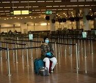 Una mujer solitaria espera frente al mostrador de una aerolínea en el aeropuerto Zaventem de Bruselas el 29 de julio de 2020.