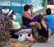 Varias personas aguardan en el suelo para entrar a una tienda y adquirir comestibles. (EFE / Yander Zamora)