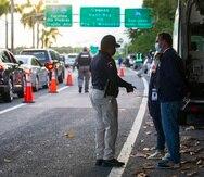 Mariengely Serrano y Javier González, de la oficina del monitor federal, conversan con el teniente Rodolfo León Morales, de la División de Tránsito y autopistas de Carolina, al llegar para observar el bloqueo de la Policía en Isla Verde.
