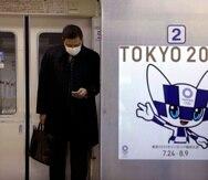Un cartel de los Juegos Olímpicos de Tokio 2020 es visto junto a la puerta un tren del metro mientras un viajero con una máscara mira su celular. (AP)