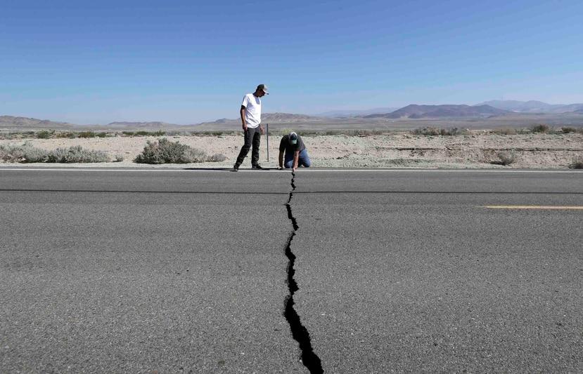 Ron Mikulaco, derecha, y su sobrino Brad Fernandez examinan una grieta causada por un sismo sobre la carretera 178 el sábado en las afueras de Ridgecrest, California. (AP/Marcio Jose Sanchez)