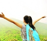 cheering hiking woman open arms at mountain peak -----