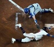 El cátcher de los Dodgers de Los Ángeles, Will Smith, no logra tocar a Eddie Rosario, de los Braves de Atlanta, en el plato en el segundo juego de la Serie de Campeonato de la Liga Nacional el domingo.