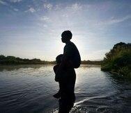 Un hombre carga a su hija al cruzar el río Bravo de Ciudad Acuña, México, a Del Río, Texas.