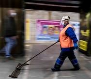 Una empleada con mascarillas y guantes limpia el piso de una estación de metro en Kiev, Ucrania.