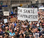 Manifestantes antivacunas desfilen en París para protestar contra las medidas más recientes del gobierno francés para combatir el incremento de infecciones con coronavirus.  (AP Foto/Michel Euler)