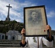 Una persona sostiene un cuadro con la foto de Francisco Franco, en el Valle de los Caídos. (AP)