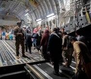 Civiles afganos abordan un avión C-17 Globemaster III de la Fuerza Aérea de los Estados Unidos, en el Aeropuerto Internacional Hamid Karzai, en Kabul, Afganistán.