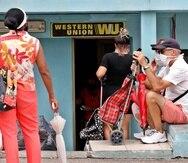 Varias personas esperan fuera de una oficina de Western Union, este jueves en La Habana, (Cuba). (EFE)