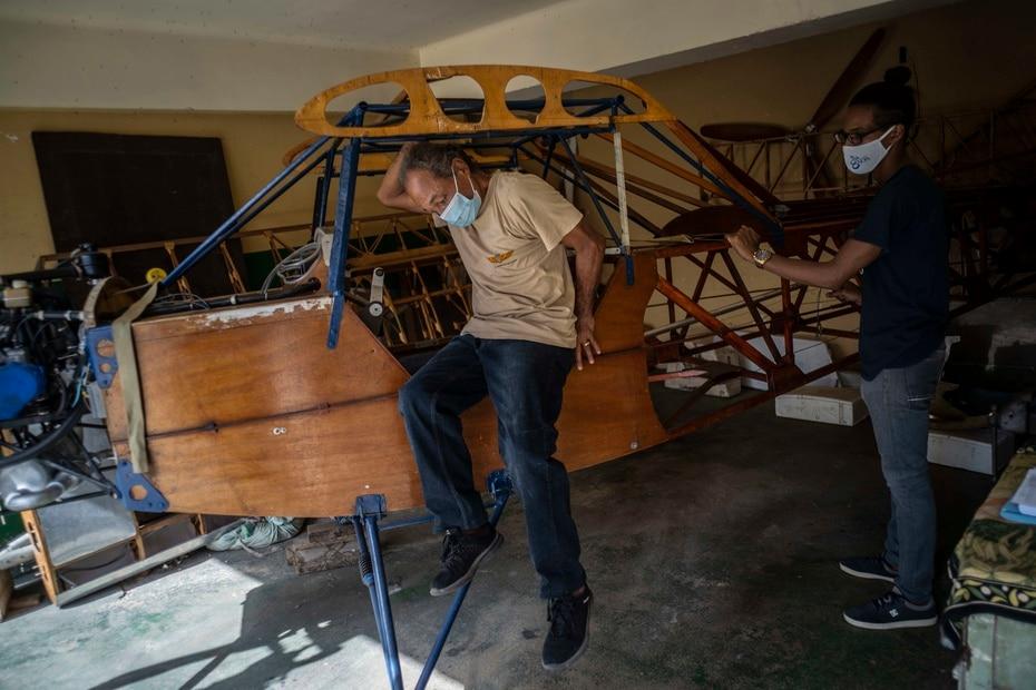 Adolfo Rivera se baja de la avioneta biplaza de madera que construyó en el garaje de su edificio de apartamentos en La Habana, Cuba.