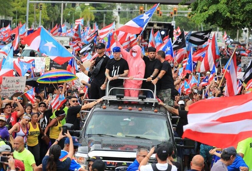 """Wisin, Residente, Bad Bunny, Nicky Jam y Julián Gil desde un vehículo, participando de la marcha """"Somos más""""."""