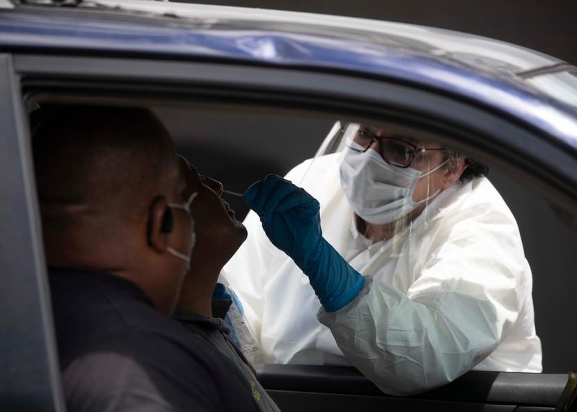 Momento en que le realizan la prueba del COVID-19 a una persona en uno de los laboratorios servicarro en San Juan.