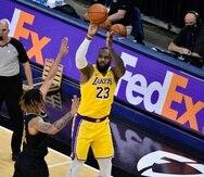 LeBron James, de los Lakers de Los Ángeles, lanza el balón sobre el alero de los Grizzlies de Memphis Brandon Clarke en el encuentro del martes.