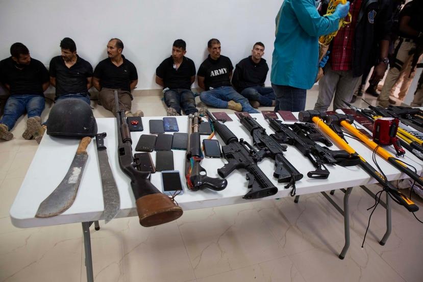 Varios de los sospechosos de participar en el asesinato de Jovenel Moïse están en el suelo, esposados, junto a parte de las armas que, supuestamente, utilizaron para llevar a cabo el magnicidio.