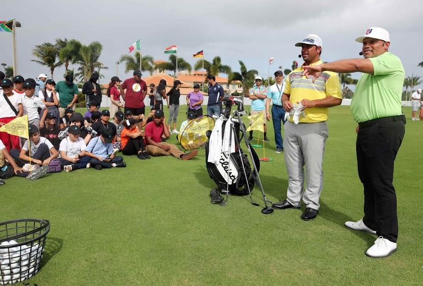 Iván Rodríguez (der.) y Rafael Campos (centro) conversan con los niños que asistieron a la clínica de golf.