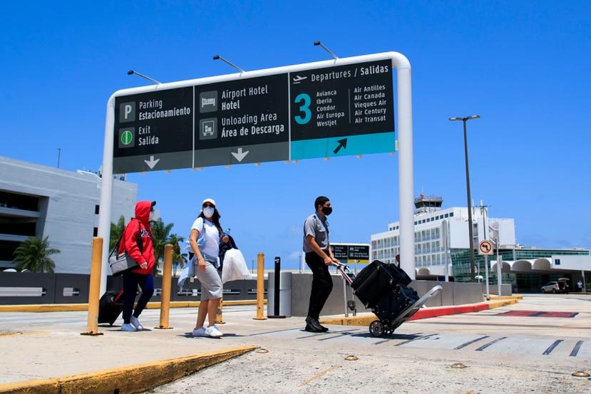 Varias personas con mascarillas en el aeropuerto internacional Luis Muñoz Marín.