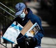 Un empleado del Servicio Postal de Estados Unidos hace una entrega con guantes y mascarilla en Filadelfia, el jueves 2 de abril de 2020. (AP / Matt Rourke)
