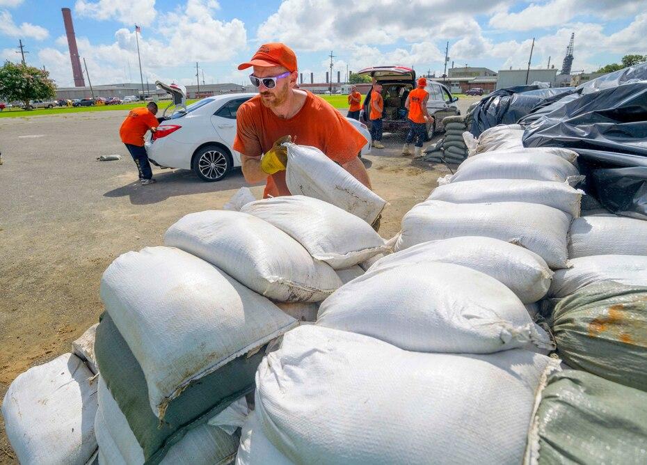Trabajadores internos de la Oficina del Alguacil de la Parroquia de St. Bernard mueven sacos de arena para regalarle a los residentes de Chalmette.  (AP)