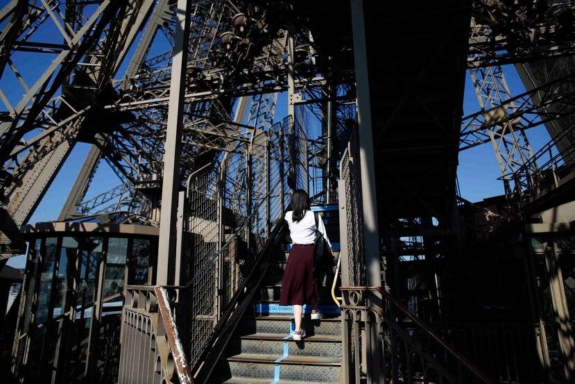 Una visitante sube las escaleras de la Torre Eiffel el día de su reapertura. (AP)