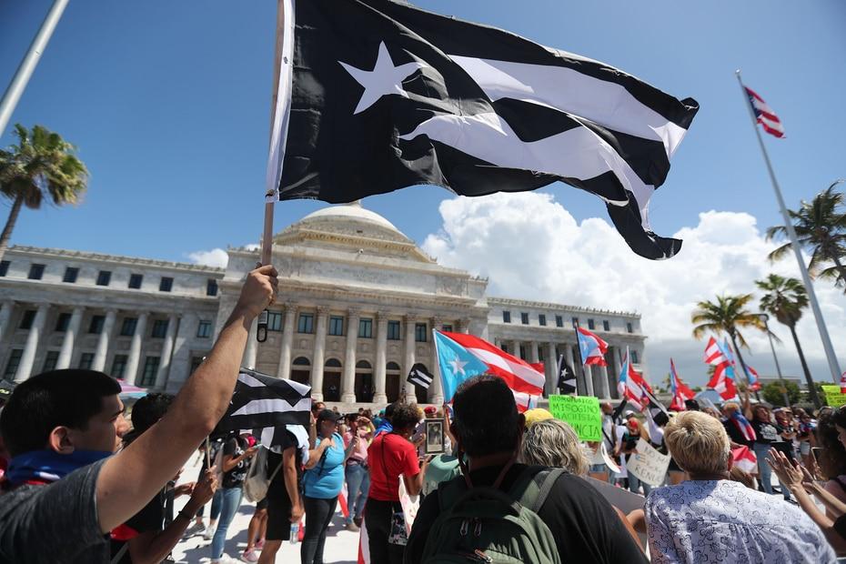Un manifestante ondea una bandera de Puerto Rico en blanco y negro frente al Capitolio antes del inicio de la marcha convocada por los cantantes Bad Bunny, Ricky Martin, Ednita Nazario y René Pérez, entre otros.