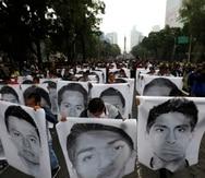 Estudiantes normalistas muestran las fotografías de los 43 estudiantes desaparecidos de la Escuela Normal Rural de Ayotzinapa al acompañar a los familiares en una marcha en 2020.